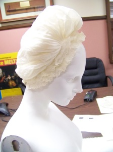 Very fine muslin cap with large caul gathered to a fixed band, ringed with lace.