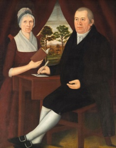 Mr. and Mrs. Brewster, seated. She wears a round-eared cap