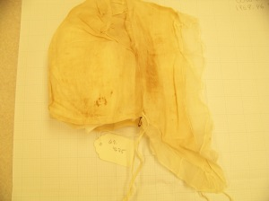 Really badly lit photo of a lappet cap with many stains and tears.