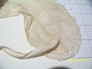 Close up of lappet end, showing lace edging and tape to tie the ends.