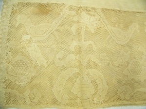 Cap McCord Museum #M980.4.26 photo by author. Close up of lace, with motif of birds and flowers.